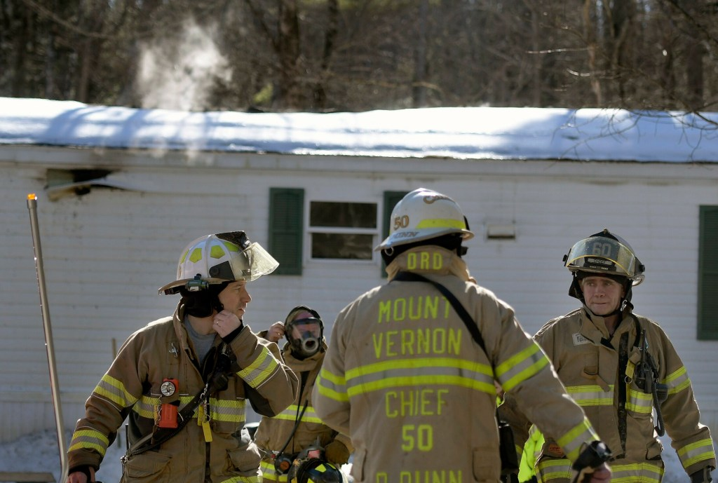 Firefighters emerge from a residence that burned Monday in Mt. Vernon.