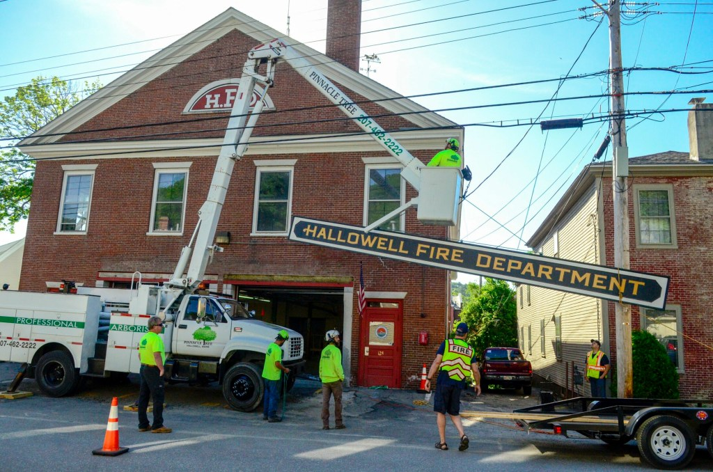 Hallowell firefighters and Pinnacle Tree Service Workers remove the sign from the old Hallowell Fire Department on Second Street on June 12, 2018, in Hallowell.