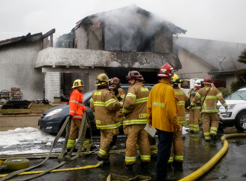 Firefighters suppress a fire at the scene of a deadly plane crash in the residential neighborhood of Yorba Linda, Calif., Sunday, Feb. 3, 2019. The Federal Aviation Administration said a twin-engine Cessna 414A crashed in Yorba Linda shortly after taking off from the Fullerton Municipal Airport.