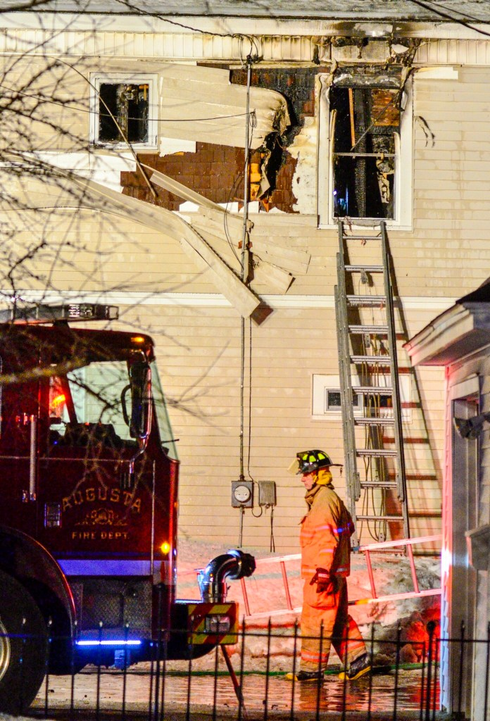 A firefighter carries a ladder back to a truck as they clear up at 6:06 p.m. after putting out a fire at 11 Densmore Court on Saturday in Hallowell. The fire was in a two-story residence at the end of Densmore Court, a short, dead-end street off Wilder Street, near Bolley's Famous Franks. The call came in at 4:24 p.m., and Augusta, Gardiner, Farmingdale and Randolph were some of the departments that responded as mutual aid. Water Street was closed between Winthrop and North streets.