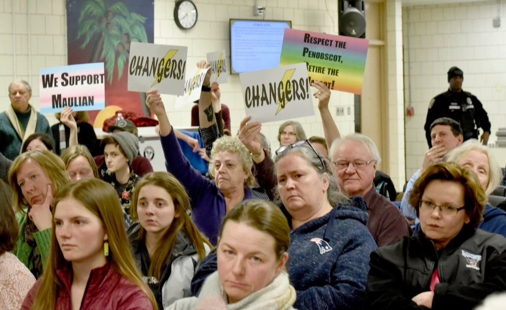 People against the use of the nickname Indian in SAD 54 schools hold signs urging school board members to vote to stop the practice during a meeting in Skowhegan on Thursday.