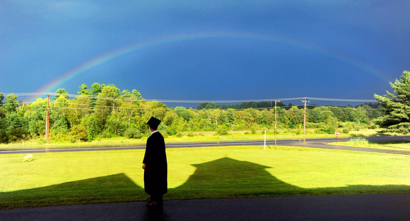 Staff photo by Michael G. Seamans Cody Buzzell, 17, stands in the shadow of Moody Chapel as a rainbow shines over Hinkley before the Maine Academy of Natural Sciences at Good Will-Hinkley inaugural commencement event on Friday, Aug. 2, 2013.
