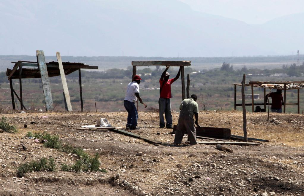 People left homeless by last month's earthquake build a new house on a hill overlooking Port-au-Prince, Haiti. As the country's rainy season nears, the government is beginning to focus on getting quake victims into permanent housing.