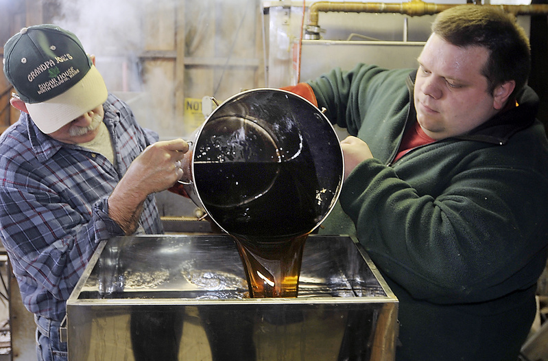 Steven McKenney and son, Ben McKenney, pour condensed maple syrup into the canning machine that will reheat, filter and prepare for bottling some of this season's syrup at Grandpa Joe's Sugar House.