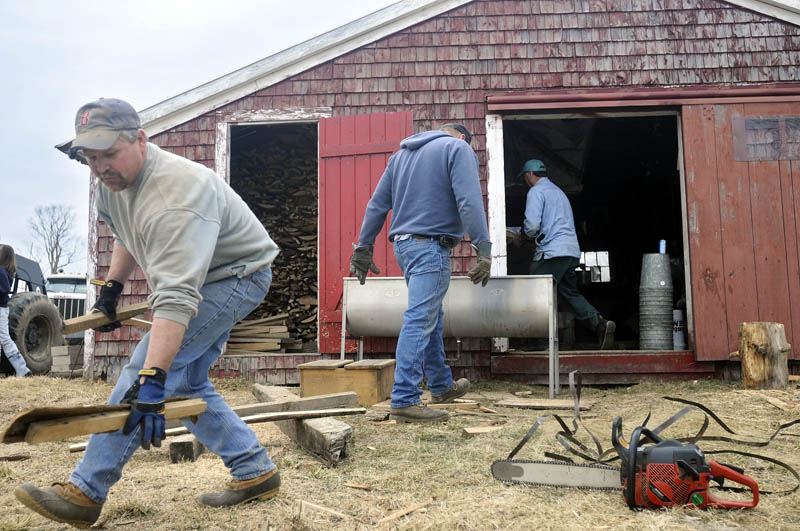 """PACKING UP: Jim Gilbert, left, collects slabs of firewood Sunday in front of Mark Fenderson's sugar shack in Whitefield. Several of Fenderson's friends helped him clean and pack up the shack after only making syrup for seven days this years. """"It was a pretty short season,"""" Fenderson said."""