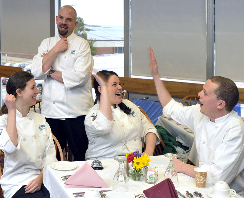 Chef Tony Poulin, an SMCC culinary arts instructor, looks on approvingly as students Cassette, Bradeen and Ault celebrate a mock-competition victory while practicing for the main event, which begins Saturday.