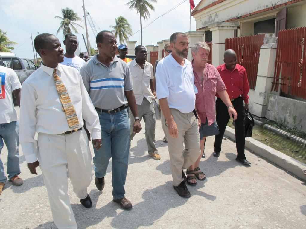 Lewiston native Father Marc Boisvert, third from left, is flanked by Sea Hunter owner Greg Brooks of Gorham as they walk from one meeting with government officials to another Wednesday in Les Cayes, Haiti.