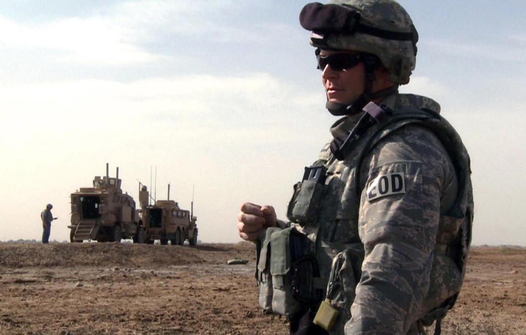Tech Sgt. Jeremy Phillips waits for his team members to prepare a detonation outside of Forward Operating Base Garry Owen on Monday in Maysan province, Iraq. In real life, bomb technicians break out their bulky bomb suits only as a last resort, preferring the safer means of disarming bombs remotely.