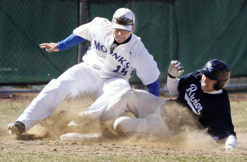 St. Joseph's third baseman Mike Pratt applies the tag to snuff out a steal attempt by Rivier's Shaun Hanson during the second game of a baseball doubleheader Saturday at Standish. The Monks won 3-1 to complete a sweep after winning the opener, 10-0.