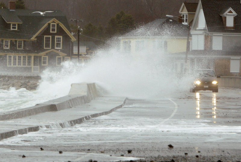 A wave crashes over a sea wall as a car makes its way along Beach Avenue in Kennebunk on Monday.