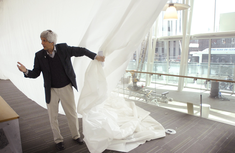 Steve Podgajny, executive director of the Portland Public Library, pulls back a drop cloth to show off the view, and the amount of sunlight, that library users will enjoy after the addition of large windows as part of a remodeling of the library.