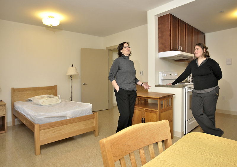 Debora Keller, left, director of development for Avesta Housing, and Amanda Wells, coordinator for Florence House, give a tour of the new home for homeless women on Valley Street last week. This is one of the independent living rooms at the facility.