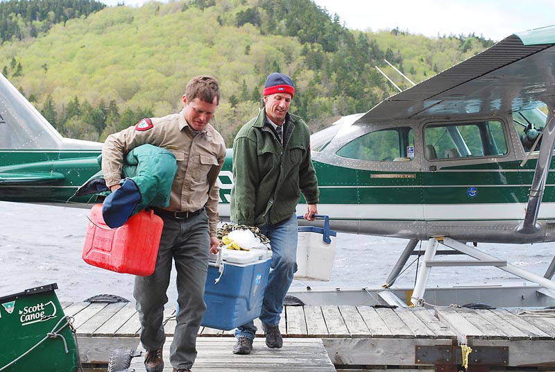 Fisheries biologist Frank Frost and pilot Igor Sikorsky carry an Arctic char caught in Big Reed Pond. The Sikorskys have provided transportation and lodging to char restoration efforts.