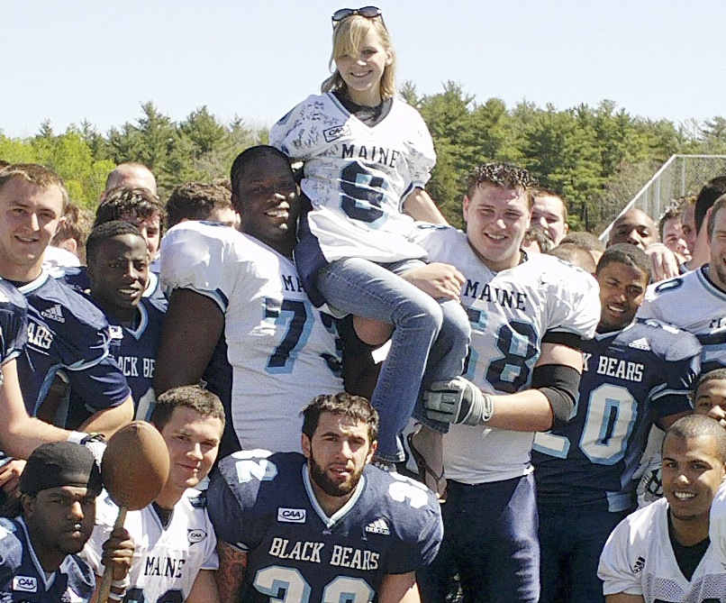 University of Maine photo Ashley Drew of Scarborough, a UMaine graduate student and passionate trumpet player, gets a lift from Tyler Patterson, left, and Steve Shea on Saturday after the annual spring football game. The team helped raise money for Drew's double lung transplant, which she needs because she suffers from cystic fibrosis.