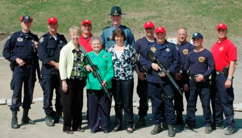 Rep. Paulette Beaudoin, D-Biddeford, holds a new AR-15 between Rep. Anne Haskell, D-Portland, and Public Safety Commissioner Anne Jordan. With them, from left, are Troopers John Davis and Lance McLeish, Sgt. William Keith, Col. Patrick Fleming, Troopers Andre Paradis and Jeff Degroot, Cpl. Ed Furtado and Troopers Eric Paquette and Jonathan Leach.