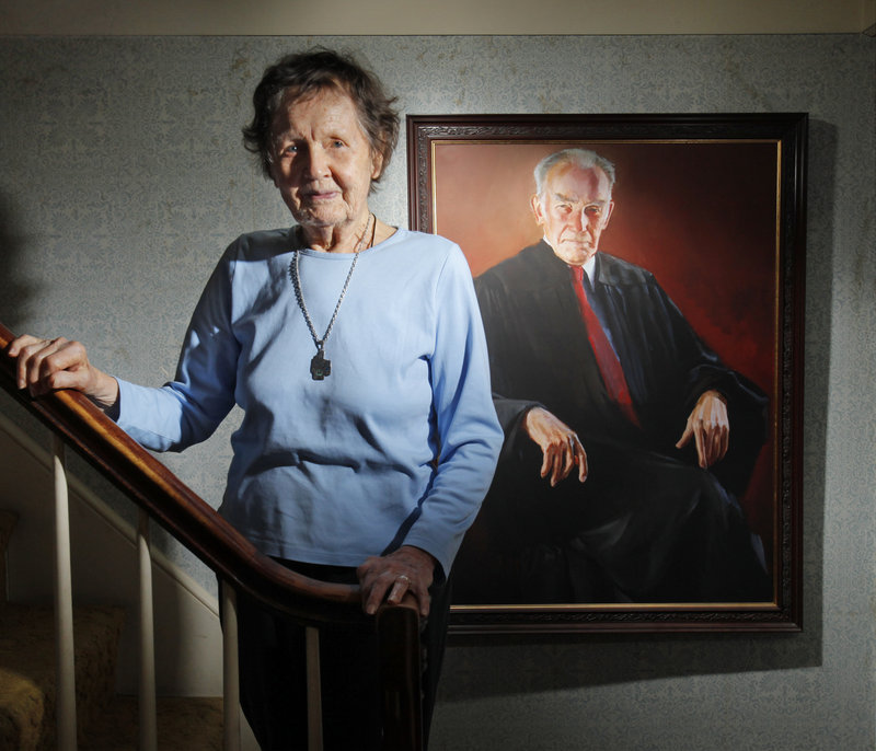 Ruth Coffin poses for a photo in her South Portland home next to a painting of her husband, Judge Frank M. Coffin, a federal appeals court judge who died in December. On Saturday, about 50 judges from around the country are expected to attend a celebration of life for Coffin.