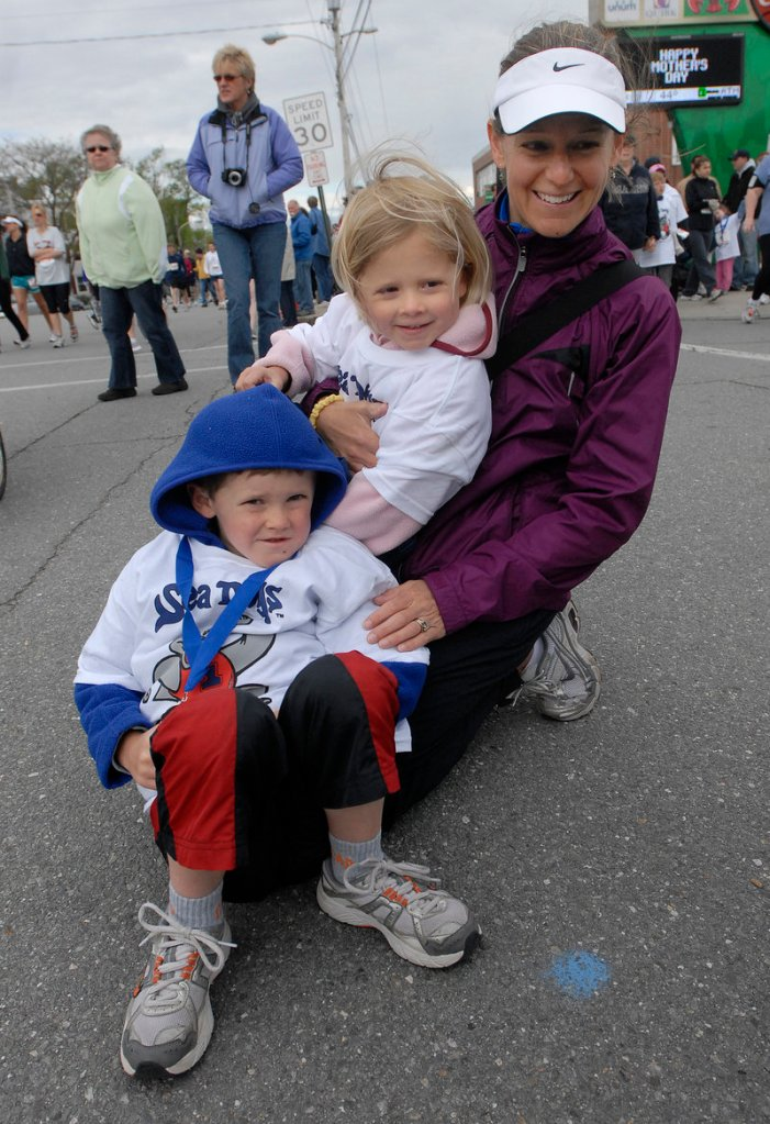 Erika Hemphill of Freeport and her children Oliver, 6, and Natalia, 3, huddle together on the sidelines Sunday in anticipation of the start of the 10th annual Sea Dogs Mother's Day 5K race.