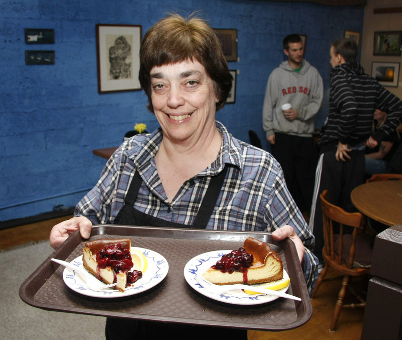 Susan Denyer, co-owner of Mr. Sandwich and Mrs. Muffin on Deering Avenue in Portland, delivers servings of New York cheesecake with fruit compote to a couple of lucky diners.