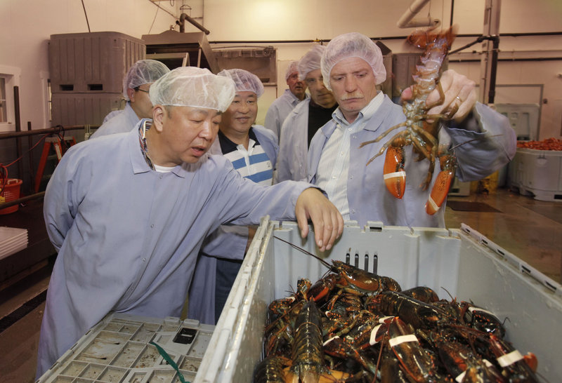 Jeffrey Holden, president of Portland Shellfish Co., holds up a lobster for Ning Gaoning, left, and other Chinese business leaders to see during their visit to Portland on Friday. Ning is the chairman of COFCO, a Chinese conglomerate that includes the country's largest food importer.