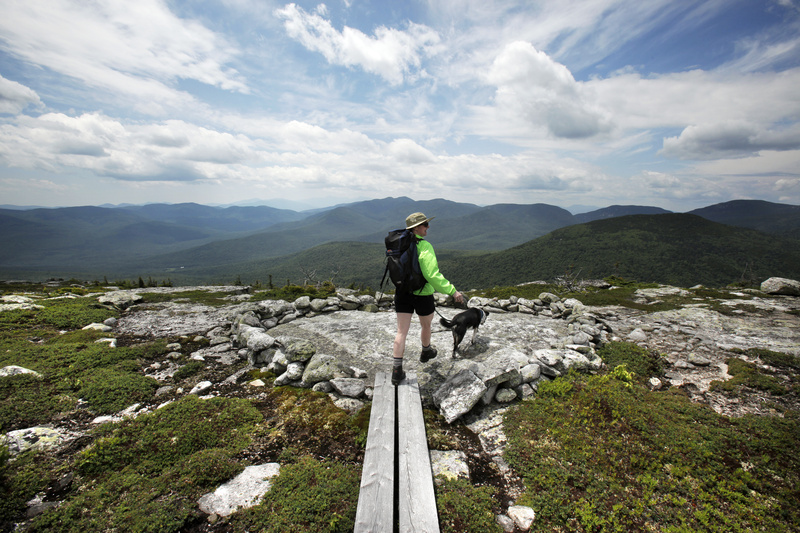 Reporter Deirdre Fleming walks out to an outlook on Sunday River Whitecap while hiking the Grafton Loop trail in Newry.