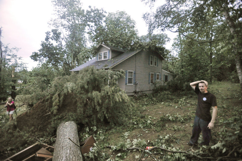 Kyle Lewis assesses the damage at his home on Fort Hill Road (Route 114) in Gorham after a severe storm raked the area. His aunt, Heather Coppola, said they were eating dinner when the sky turned black and they saw a funnel cloud forming.