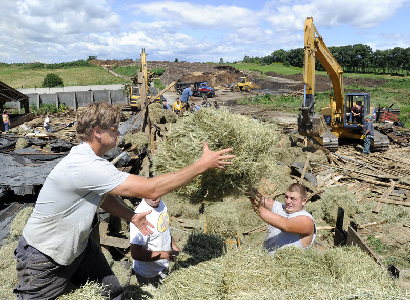 Art McNeally, Jason Mitsin and Nate Faulkner load hay onto a truck Thursday at the Benson dairy farm in Gorham. The three men were among dozens of friends, relatives and neighbors who helped the family clean up after Wednesday's storm.