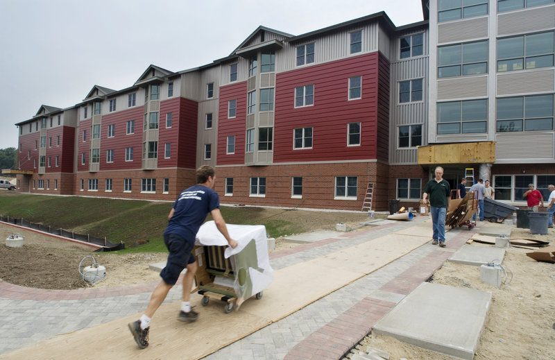 A mover pushes a chair into a new dorm – a 300-bed suite-style residence hall – at the University of New England campus in Biddeford last week.