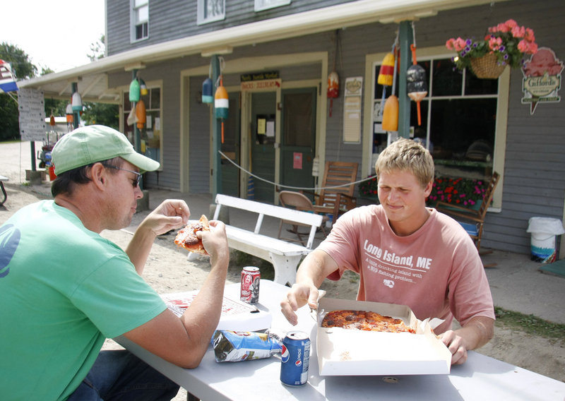 Steve Train, left, of Long Island, captain of the lobster boat Hattie Rose, and Alex Anderson, also of Long Island and sternman on Hattie Rose, stop for pizza they special ordered at Pearls Seaside Market.