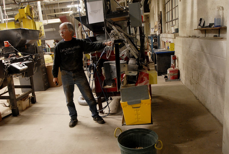 """Longtime employee Foster Davis demonstrates an automatic sorter at the Saunders Brothers mill in Locke Mills on Monday. """"I can get every machine running here in 10 minutes,"""" he said."""