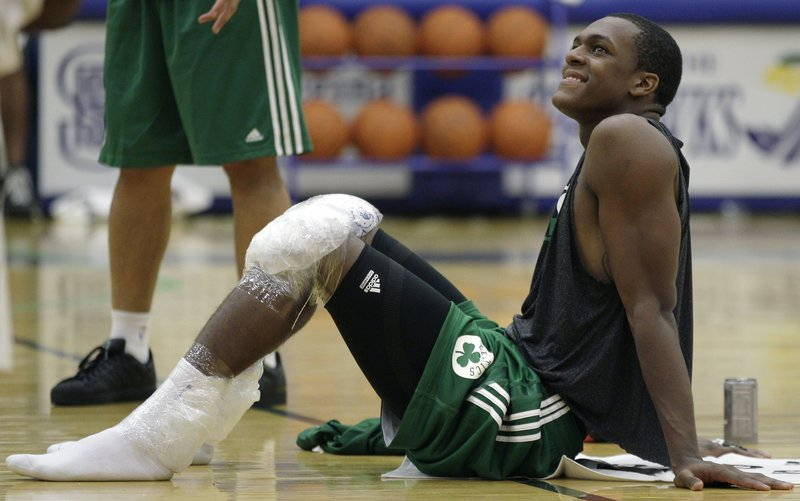 Celtics guard Rajon Rondo smiles as he rests on the court with his knees iced after their practice at the team's training camp at Salve Regina University in Newport, R.I.