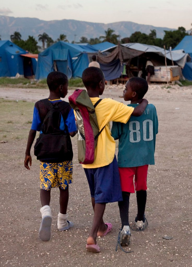 Elisee Anderson, right, and his friends walk home earlier this month after soccer practice next to a refugee camp for people displaced by the earthquake at a sports complex in Port-au-Prince. On Friday, an isolated storm destroyed an estimated 8,000 tarps, tents and shacks in the capital and killed at least six people, including two children.
