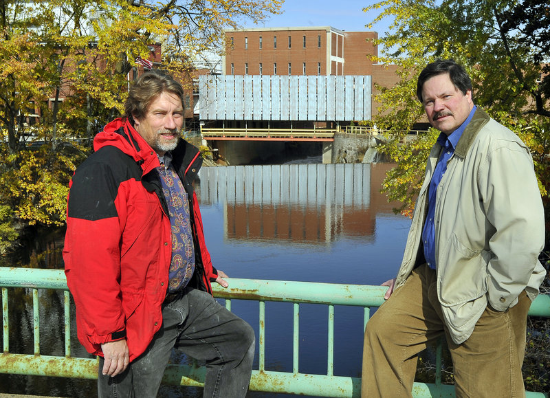 The founders of Friends of the Presumpscot River, Mike Shaughnessy and Will Plumley, frame the dam at Sappi in Westbrook that will soon have a passageway for fish.