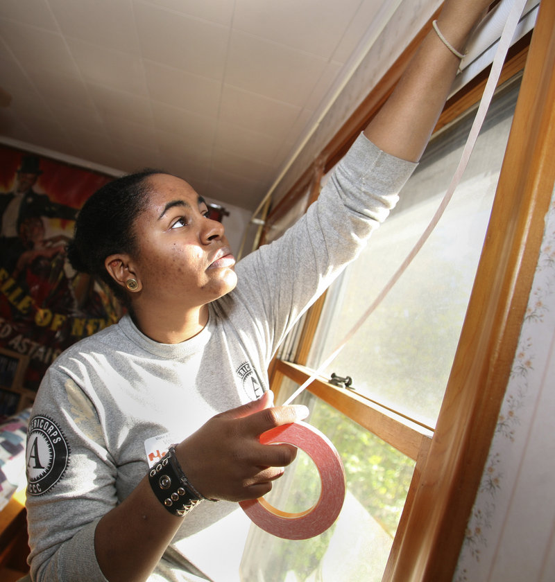 Mercedes Porter, a volunteer AmeriCorps NCCC worker from California, weatherizes a window at the home of Dick Dinman on Highland Avenue in Scarborough on Saturday.