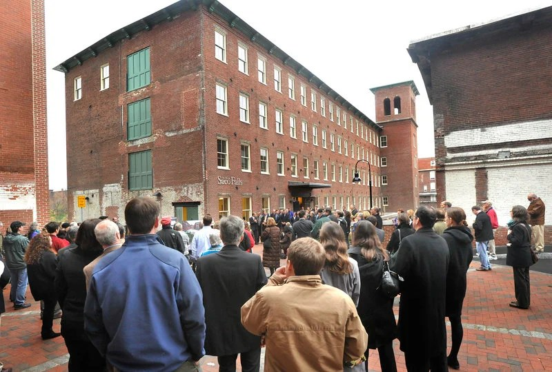 A crowd of residents, officials and business people attends an open house for The Mill at Saco Falls, a 66-unit mixed-income residential development in a refurbished mill building in Biddeford, on Monday.