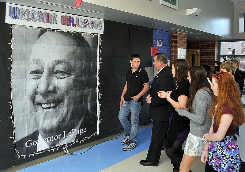 Sam Luebbert, left, leads Paul LePage to a computer-generated photo on a welcome wall at Lyman Moore Middle School. He asked LePage to sign the photo and write a message.