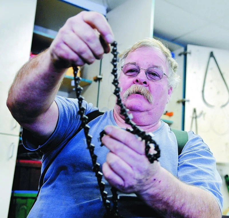 David Lancaster unfurls a chain for a saw Sunday at his South China workshop.