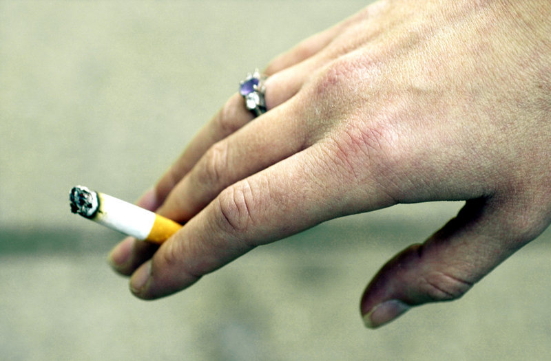 A teen smoker holds a cigarette outside Portland High School in this file photo.