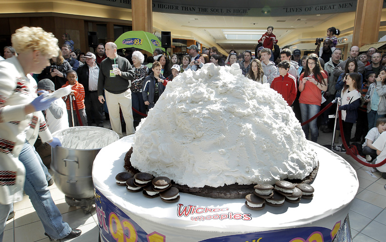 Amy Bouchard, owner of Wicked Whoopies, far left, puts the final dollops of filling on the over the 1,067-pound whoopie pie before adding the top devil's food layer at the Maine Mall in South Portland today. Competing with Pennsylvania's 250-pound pie, Maine is looking to make the whoopie pie the state's official treat.