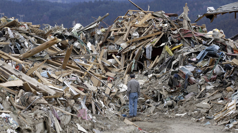 A man searches through the rubble left by the March 11 quake and tsunami in Rikuzentakata, Japan. Up to 25,000 people are believed to have died in the disasters, which also precipitated the country's nuclear crisis.