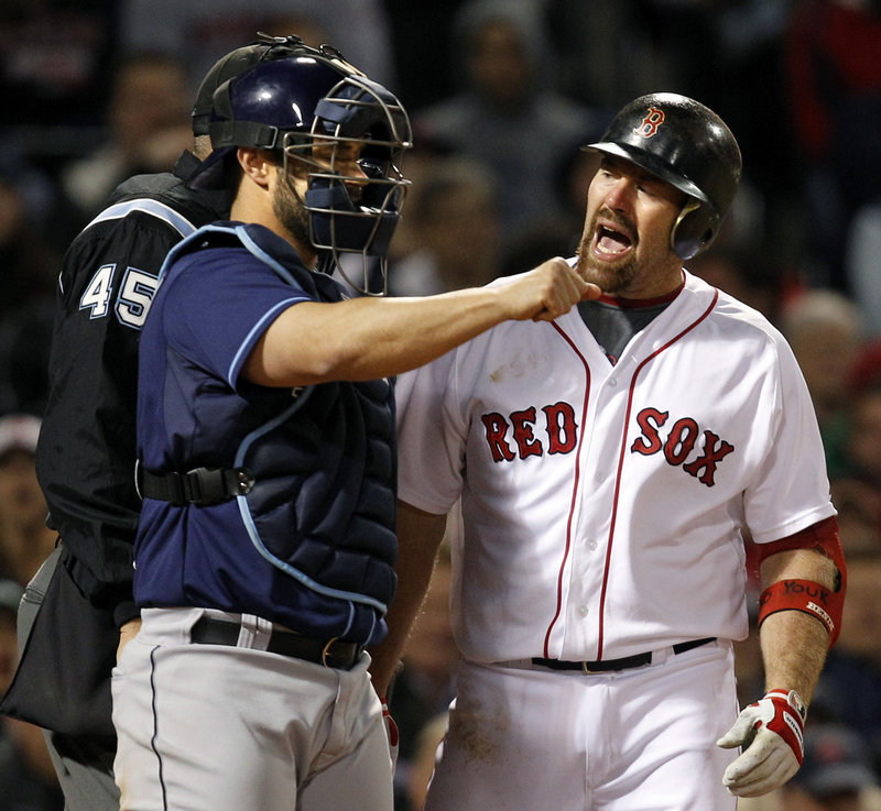 Tampa Bay catcher Kelly Shoppach throws the ball back to the pitcher as Boston's Kevin Youkilis argues a third-strike call with the plate umpire Tuesday night in the Rays' 3-2 victory.