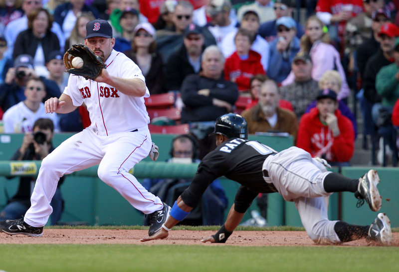 Boston's Kevin Youkilis, left, takes the throw to nail Toronto's Corey Patterson trying to steal third base in the eighth inning of an 8-1 Red Sox win at Fenway Park on Sunday.