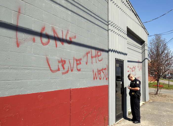 """Officer Gavin Hillard writes down contact information at a mosque on Anderson Street in Portland today where someone spray painted graffiti on the wall in the wake of Osama bin Laden's death. The writing says """"Osama today Islam tomorow (sic),"""" and """"Long live the West."""""""