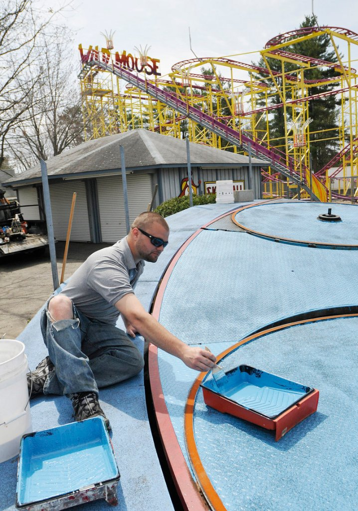 Chaz Cormier, one of many family members affiliated with Funtown/Splashtown, applies new paint to the Tilt-A-Whirl.