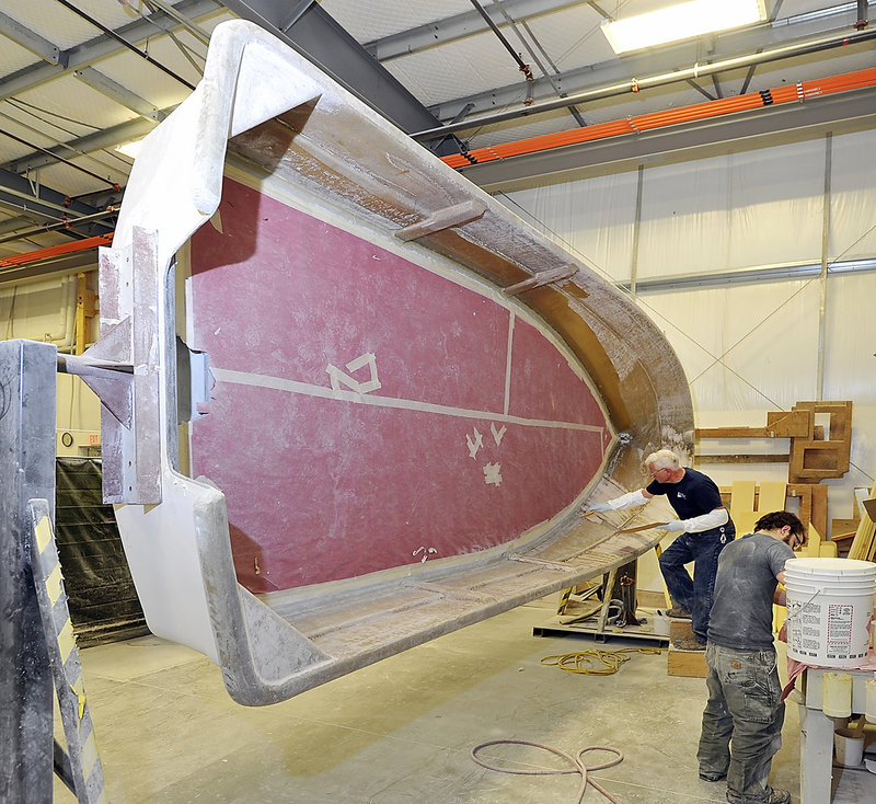 Interior finishers prepare the hull of a Maritime Marine boat at Kenway Corp. in Augusta, which makes fiberglass boats, tanks and pipe. Since 2003, Kenway has purchased two boatbuilding companies.