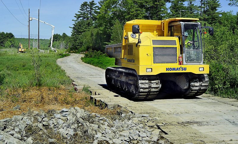 A Komat'su track dump – a specialized dump truck with tractor treads – crosses a wooden mat near a CMP work site.