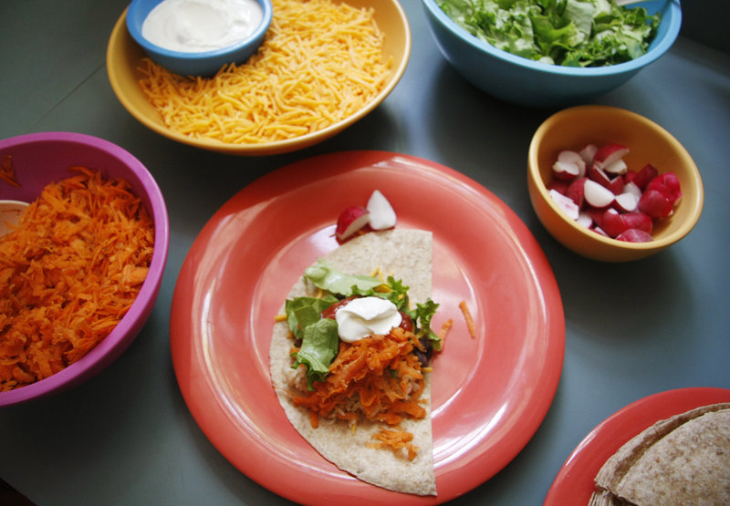 Fresh and local fixings, including grated carrots and shredded greens, are assembled for a rice and bean burrito lunch to be served to the children at the Youth & Family Outreach daycare center in Portland.