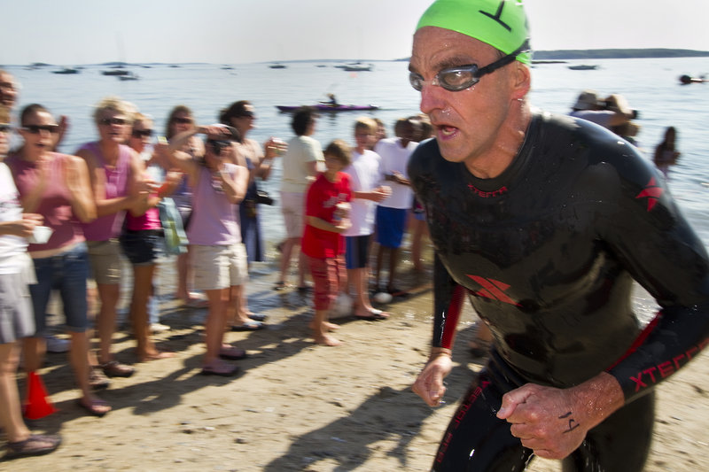 """Scott Yeomans, 47, reaches the beach as the first out of the water to win the Peaks to Portland. """"You have to stay focused on your stroke and keep going,"""" he said."""