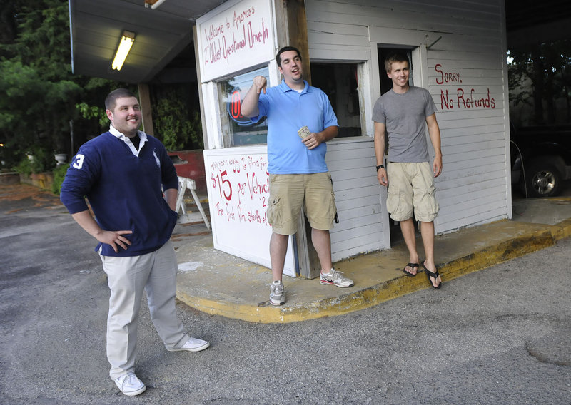 "Ry Russell, Tyler Wells and Patric Brophy, University of Southern Maine marketing students and managers of the Saco Drive-In, talk with customers at the entrance Friday. ""You can't beat it as a family coming here,"" Wells said."