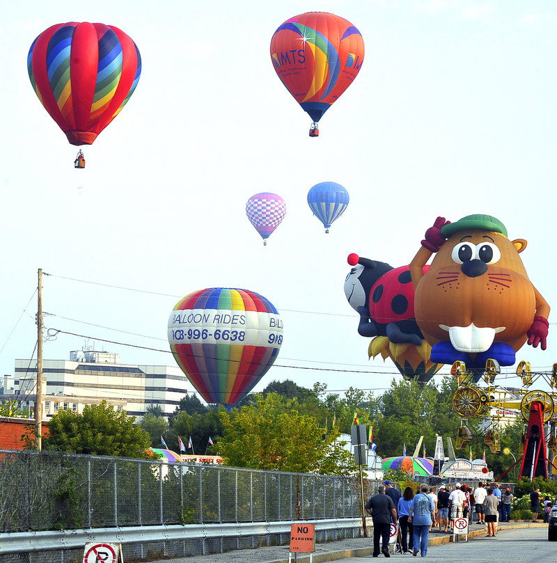Early risers watch as hot air balloons are launched carrying passengers who paid $200 to $225 each to take a ride from Railroad Park in Lewiston on Saturday.