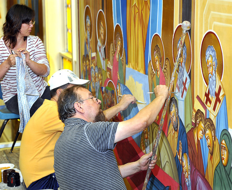 George S. Papastamatiou, right, adds details to a mural depicting the Dormition of the Virgin Mary, as his wife, Brunilda Rizaj-Papastamatiou, left, and his assistant, Christos Kazanzides, help finish the original creation.